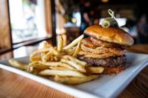 Grass-fed beef burger with fried green tomatoes, onion rings, pimento cheese spread, and bacon jam on a brioche bun.