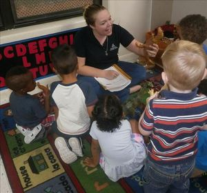 """During our """"Dinosaur"""" theme, Discovery Preschool teacher Ms. Meagan is having circle time, helping the children identify and learn about dinosaurs."""