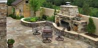 Backyard patio designed with stone pavers, dining area, and fireplace at a residence in Colorado Springs, CO.