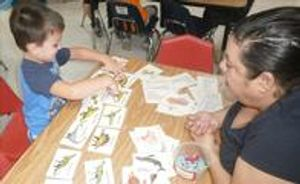 """Ms. Laurie is working with 4 year old Kayden in identifying and learning about dinosaurs during our """"Dinosaur"""" theme."""