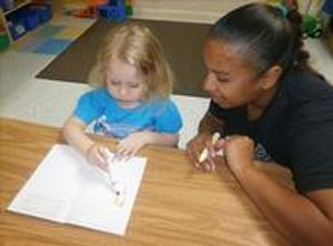 Ms. Priscilla is working with Mackenzie in her journal, helping her write her name.