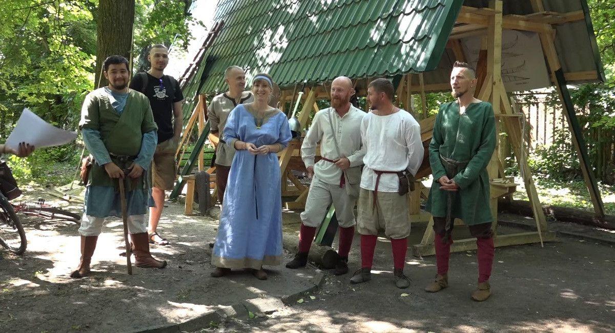 Ініціатори будівництва драккара вікінгів «Гунгнір» у м. Рівне в так званому «давньоруському» одязі (на фото човен-дракон під навісом)