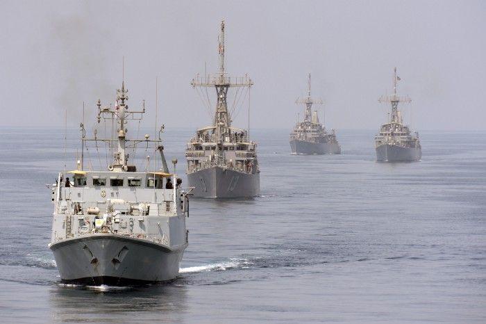 Изображение Minehunter, работающего в Персидском заливе, с тремя другими типами кораблей.