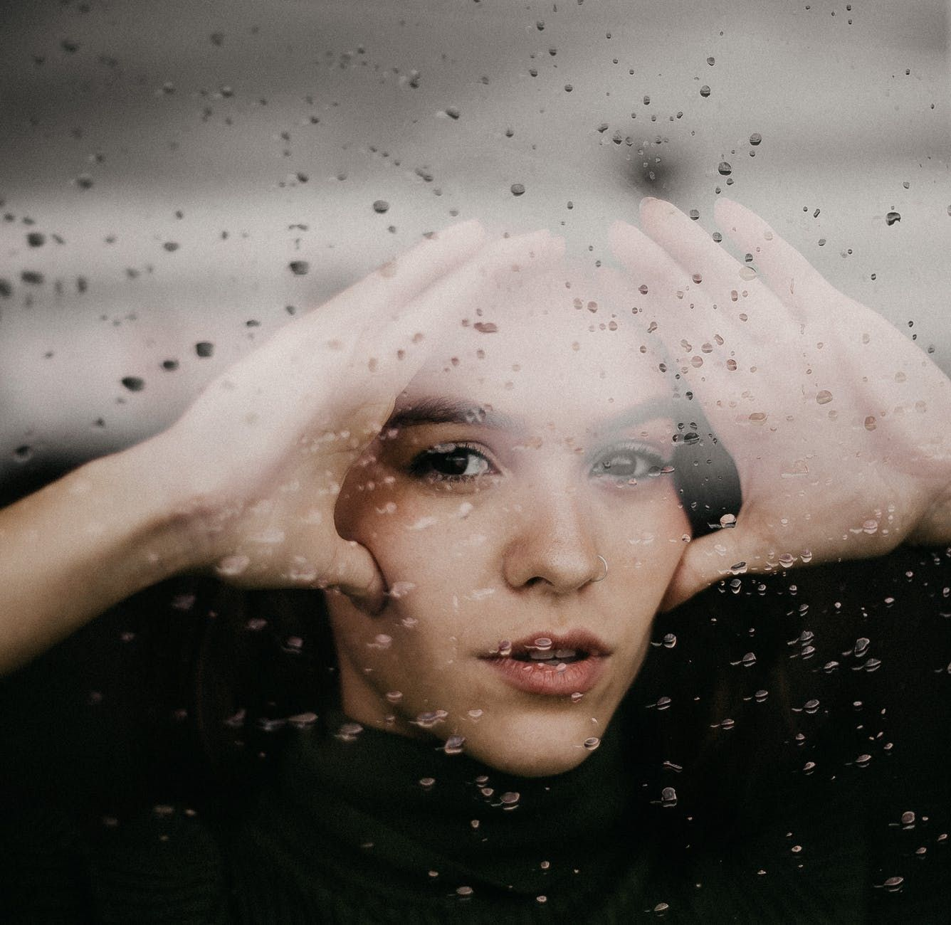 pensive female standing behind glass window with drops of water