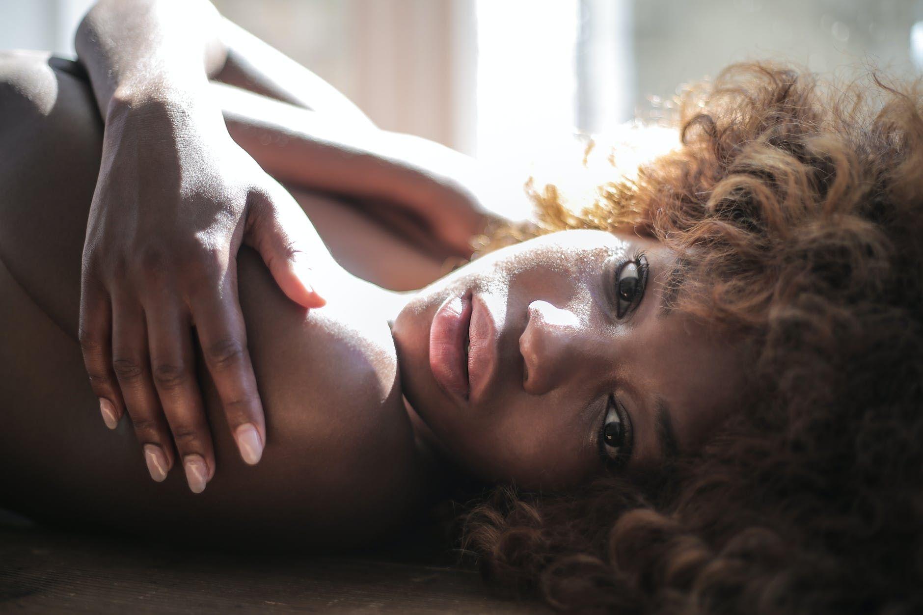 topless woman lying on floor in daylight