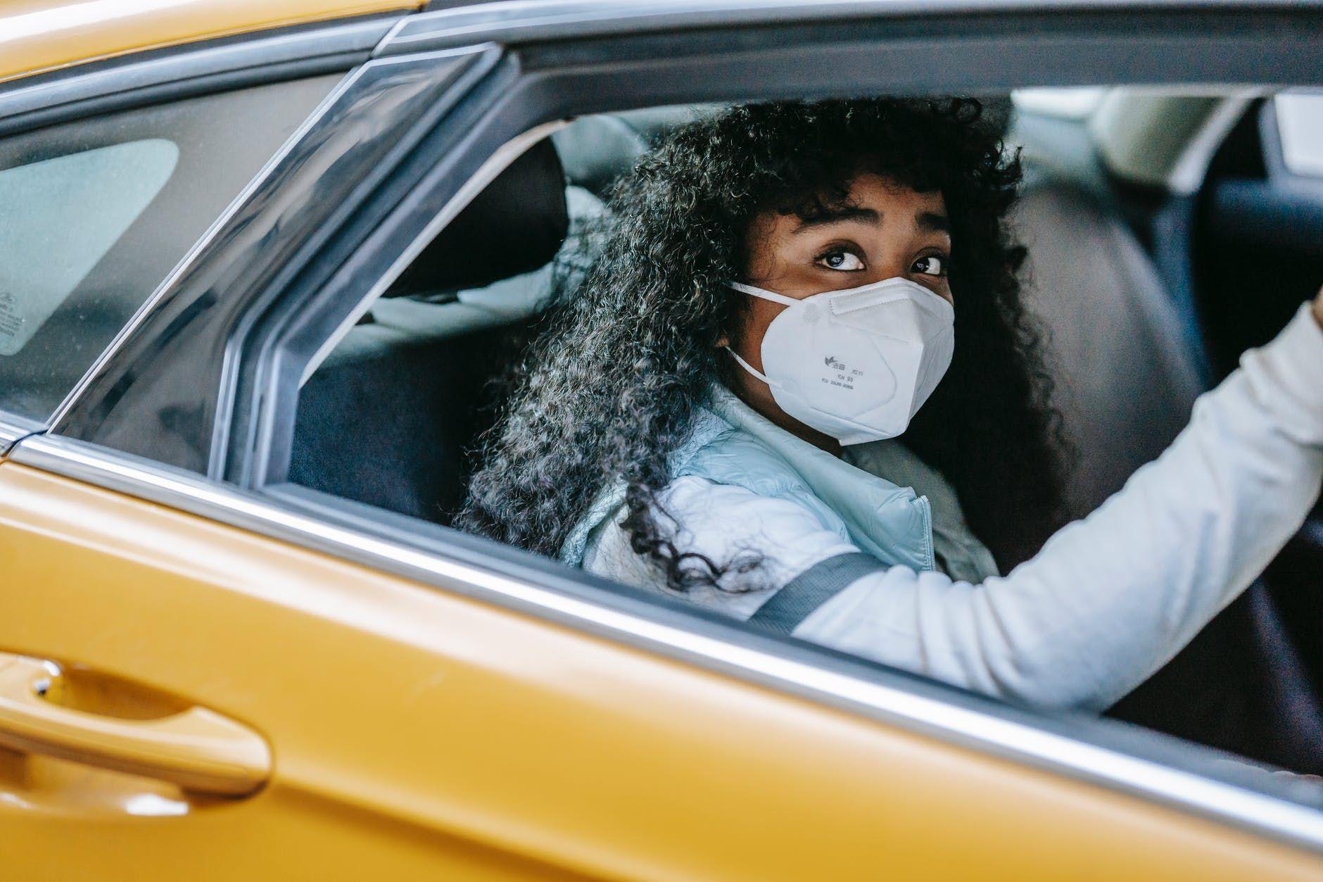 black female in mask in yellow car