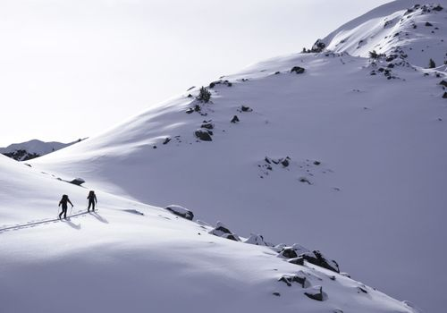 Two Ski Touring Skiers Approach Mountain Pass.  ProPhoto RGB.