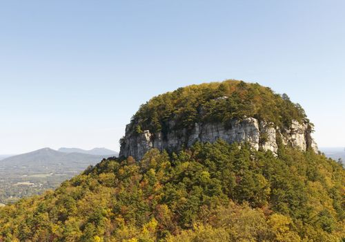 The pinnacle, in NC, 1400 feet above the valley floor, is quartzite metamorphic rock produced millions of years ago by pressure and heat below earth's surface,