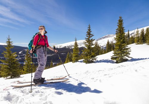 A woman touring in the backcountry on a splitboard.