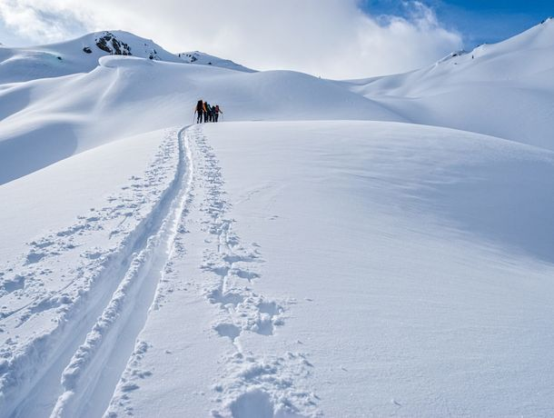 Ski Touring in the Canadian Rockies - Backcountry skiers earning their turns in the Selkirk Mountains, British Columbia, Canada.
