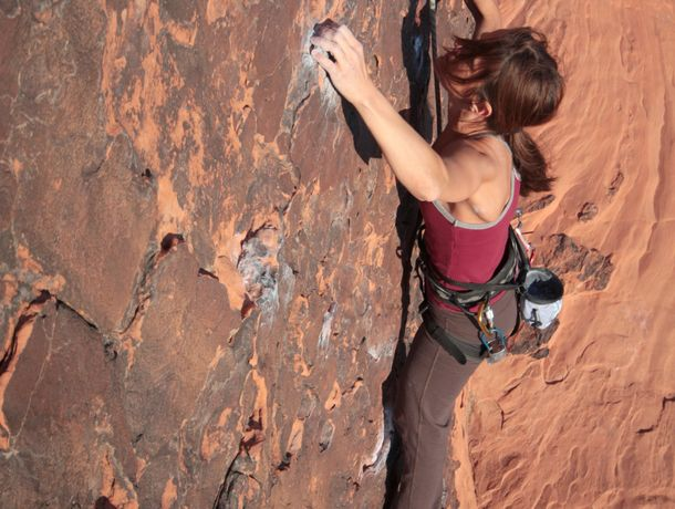 Battling her fears, a girl moves up a rock face.