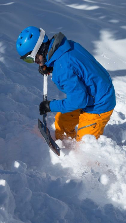 Man digging in simulated avalanche debris.