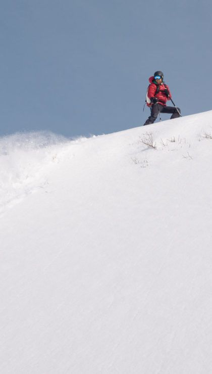 Male skier looking at a snow avalanche in the mountains