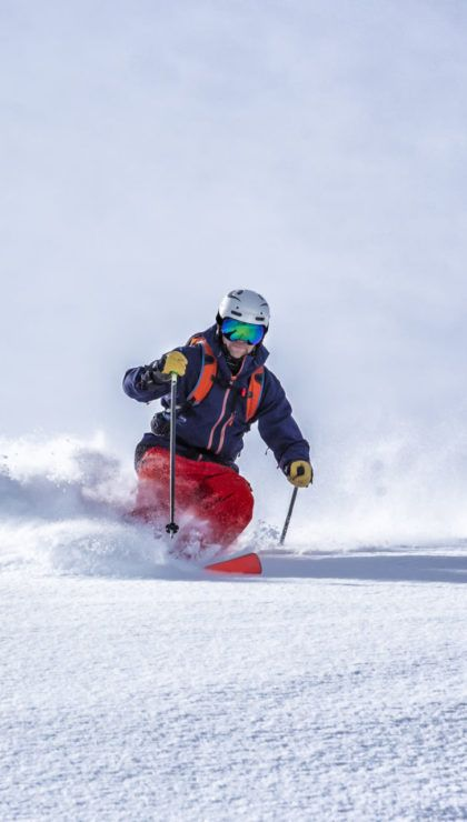 Expert backcountry skier going fast through fresh powder snow