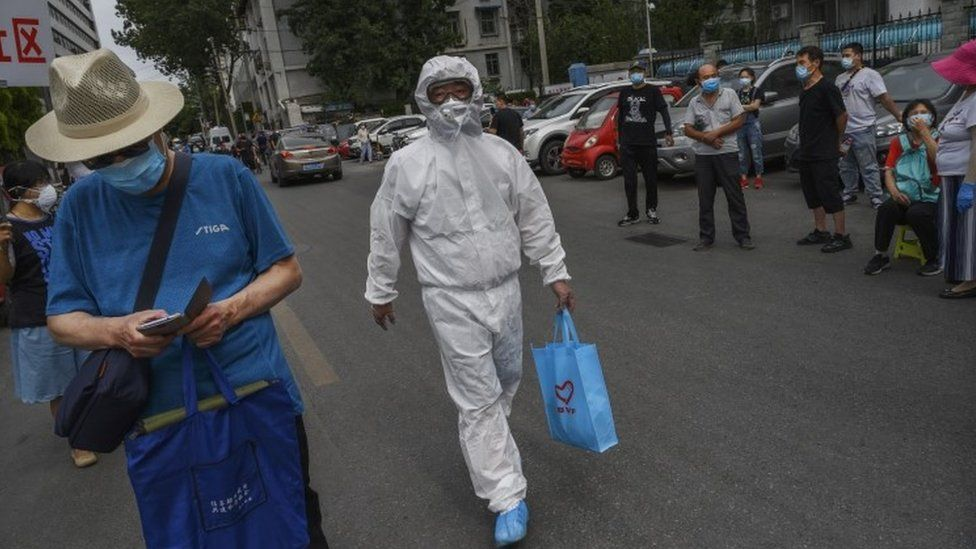 A health worker in Beijing holds a blue bag of medical devices.