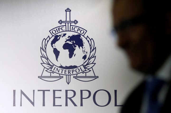 FILE PHOTO: A man passes an Interpol logo during the handing over ceremony of the new premises for Interpol's Global Complex for Innovation, a research and development facility, in Singapore September 30, 2014.