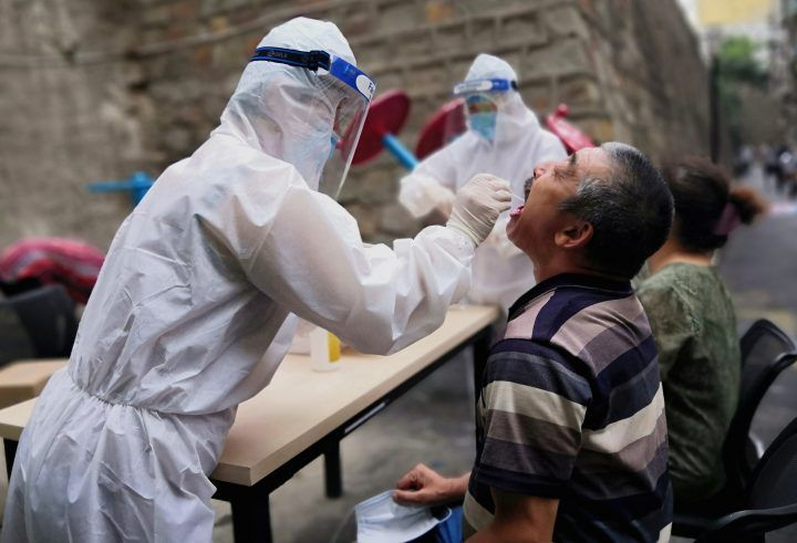A medical worker in protective suit collects a swab from a man to conduct free nucleic acid tests for residents in the residential compound, after new cases of coronavirus disease (COVID-19) were found in Urumqi, Xinjiang province, China July 19, 2020. Picture taken July 19, 2020.