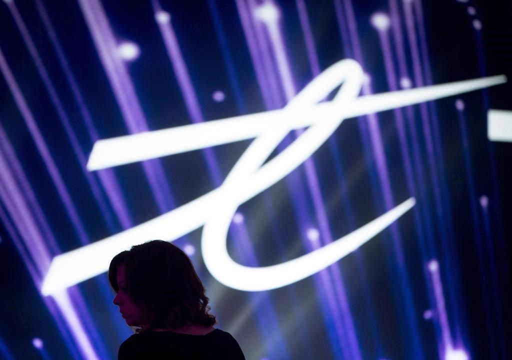 A woman is silhouetted as the Telus Corp. logo is displayed on a screen during a company event in Vancouver on Friday, October 2, 2015. THE CANADIAN PRESS/Darryl Dyck.