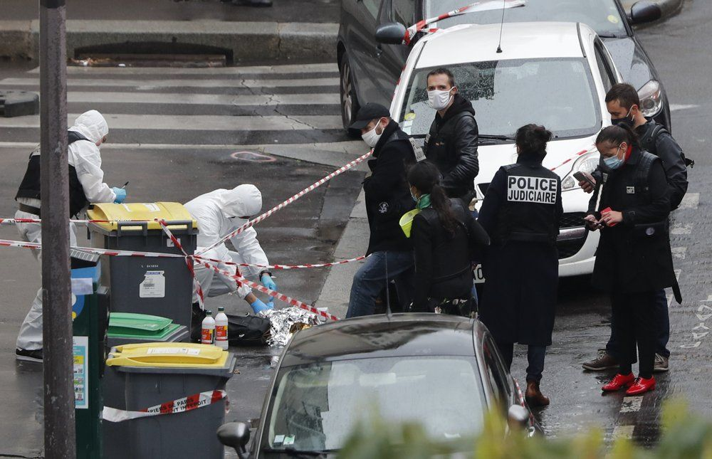 Police officers gather in the area of a knife attack near the former offices of satirical newspaper Charlie Hebdo, Friday Sept. 25, 2020 in Paris. Paris police say they have arrested a man suspected of a knife attack that wounded at least two people near the former offices of satirical newspaper Charlie Hebdo. Police initially thought there were two attackers but now say there was only one.