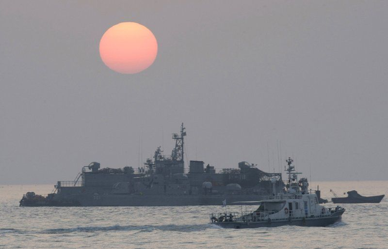 FILE - In this Dec. 22, 2010, file photo, a government ship sails past the South Korean Navy's floating base as the sun rises near Yeonpyeong island, South Korea. A South Korean official who disappeared off a government ship near the disputed sea boundary with North Korea this week may be in North Korea, South Korea's Defense Ministry said Wednesday, Sept. 23, 2020.