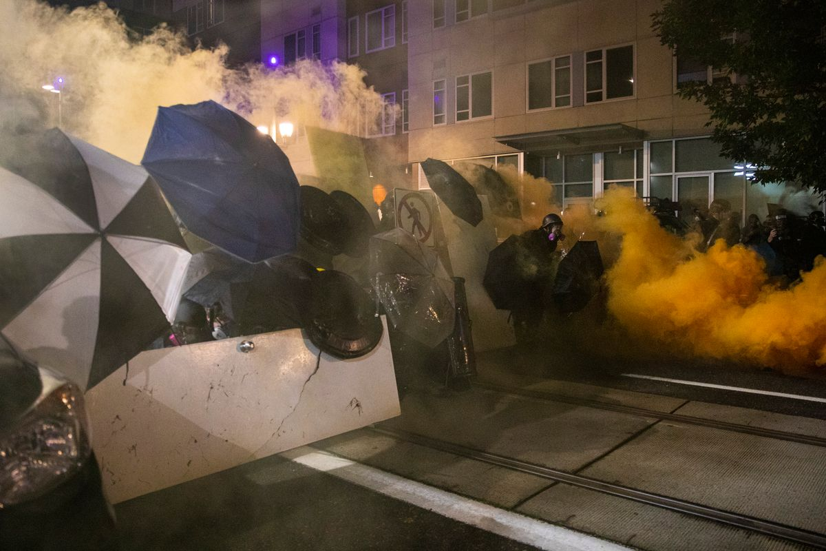 Tear gas fills the air during protests, Friday, Sept. 18, 2020, in Portland, Ore.