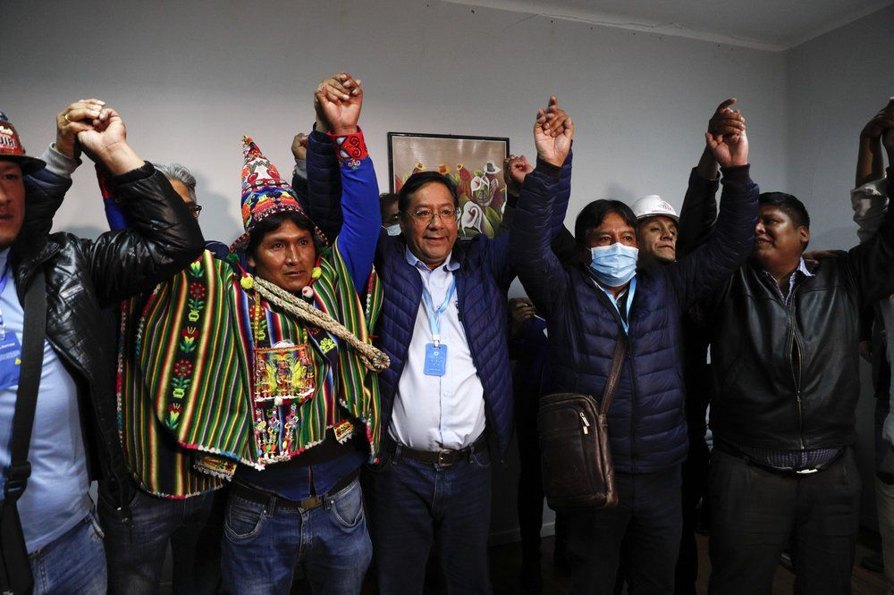 Luis Arce, center, Bolivian presidential candidate for the Movement Towards Socialism Party, MAS, and running mate David Choquehuanca, second right, celebrate during a press conference where they claim victory after general elections in La Paz, Bolivia, Monday, Oct. 19, 2020.