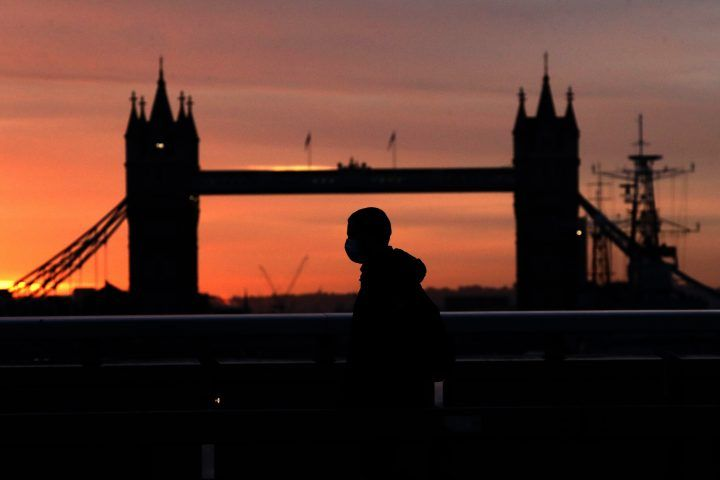 A person wearing a face mask to try to stop the spread of coronavirus walks across London Bridge, with Tower Bridge in the background, at sunrise in London, Monday, Oct. 12, 2020.