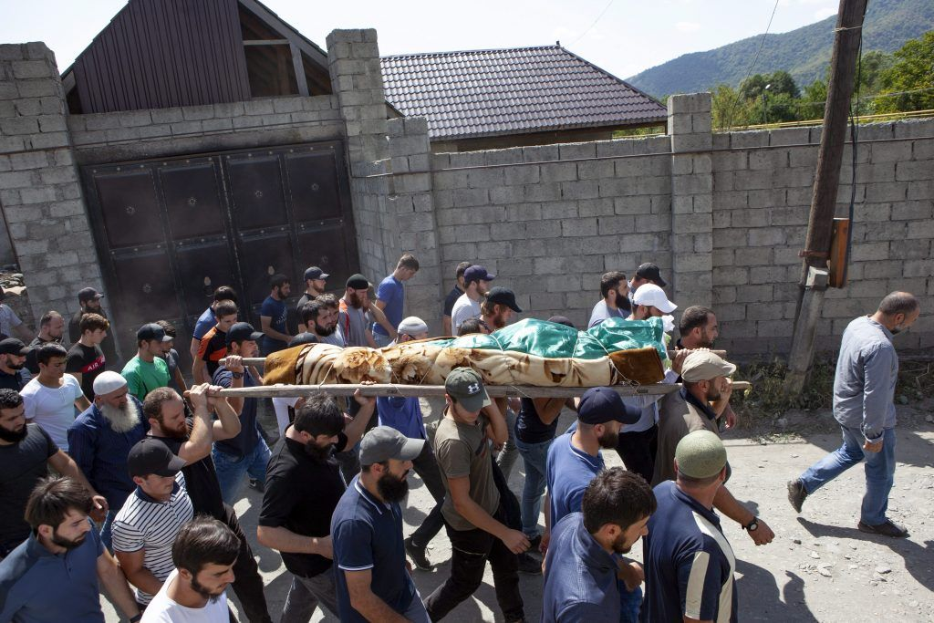 FILE-In this Aug. 29, 2019 file photo people carry the body of the victim who has been identified as Zelimkhan Khangoshvili, a Georgian Muslim during the funeral in Duisi village, the Pankisi Gorge valley, in Georgia.