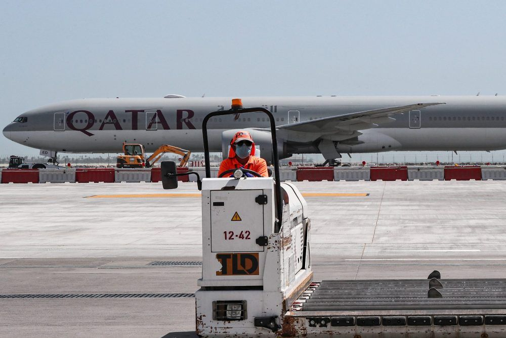 An airport worker mans a luggage trolley while behind him is seen a Qatar Airways Boeing 777 aircraft at Hamad International Airport in the Qatari capital Doha on April 1, 2020.