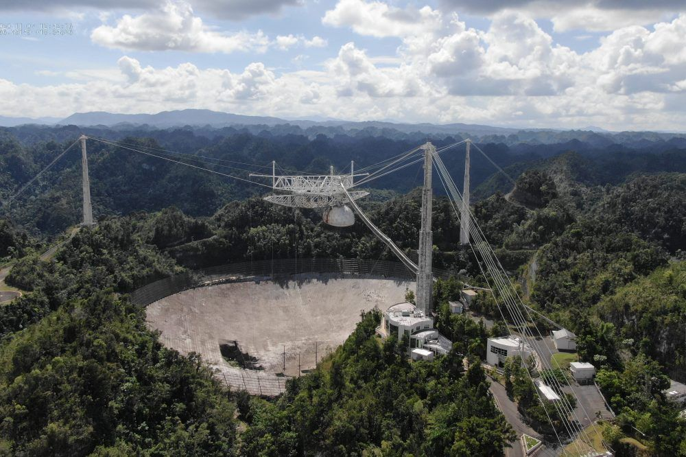 The Arecibo Observatory is shown with a large hole in its telescope dish in November 2020.
