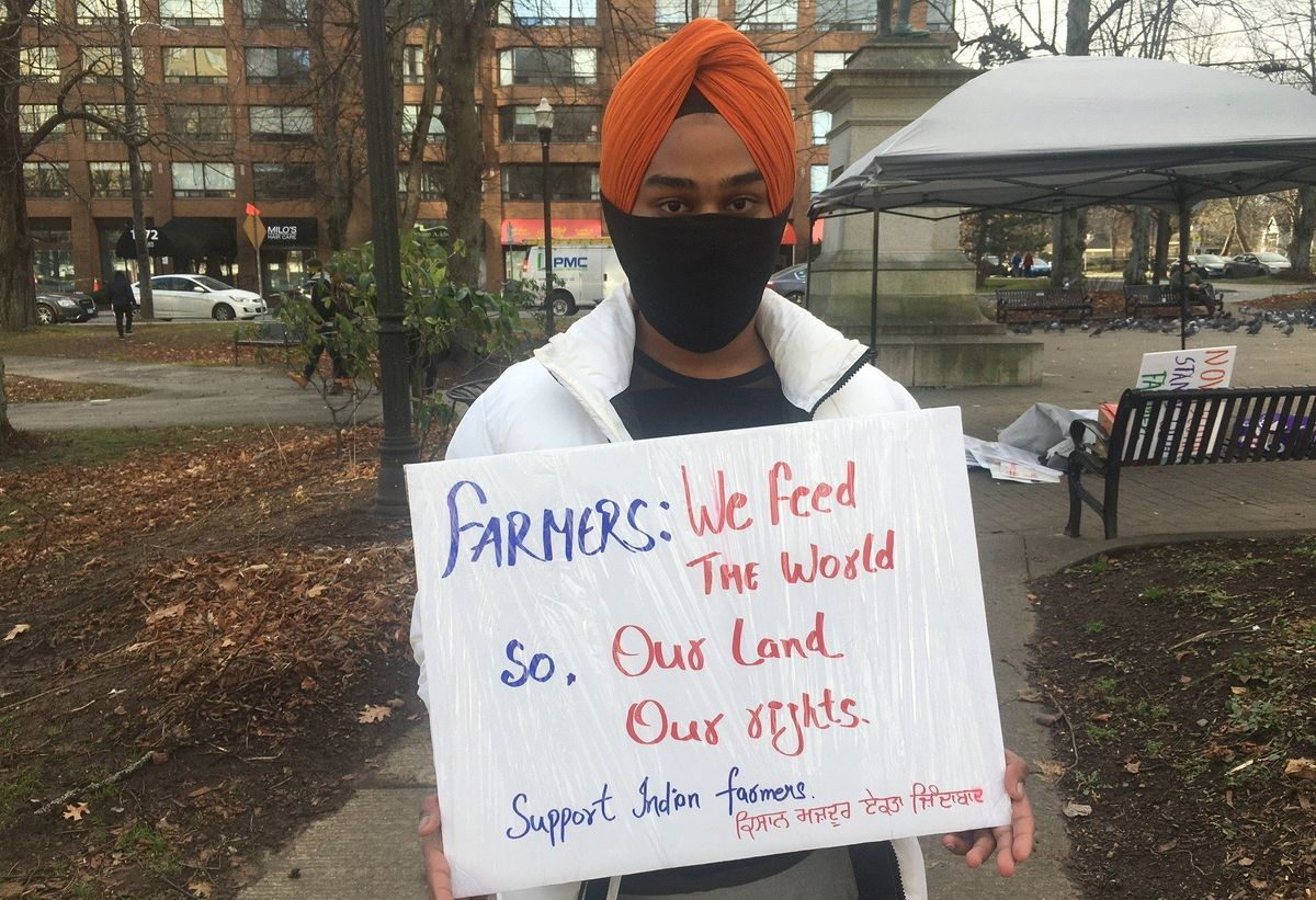 A protestor is holding a sign in Halifax in solidarity with Indian farmers protesting new agriculture laws.