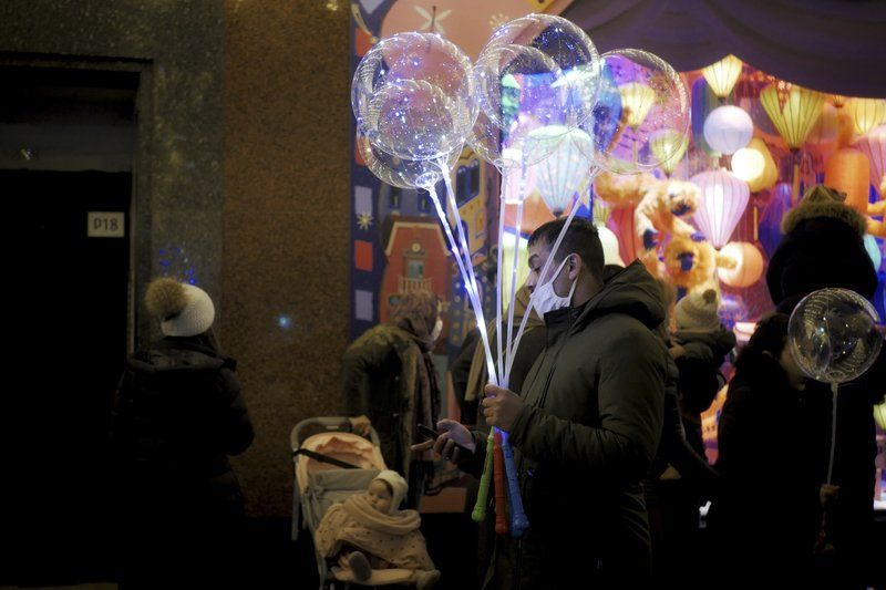 A man holds light balloons as he checks his phone on a sidewalk next to a department store in Paris, Thursday, Dec. 31, 2020.