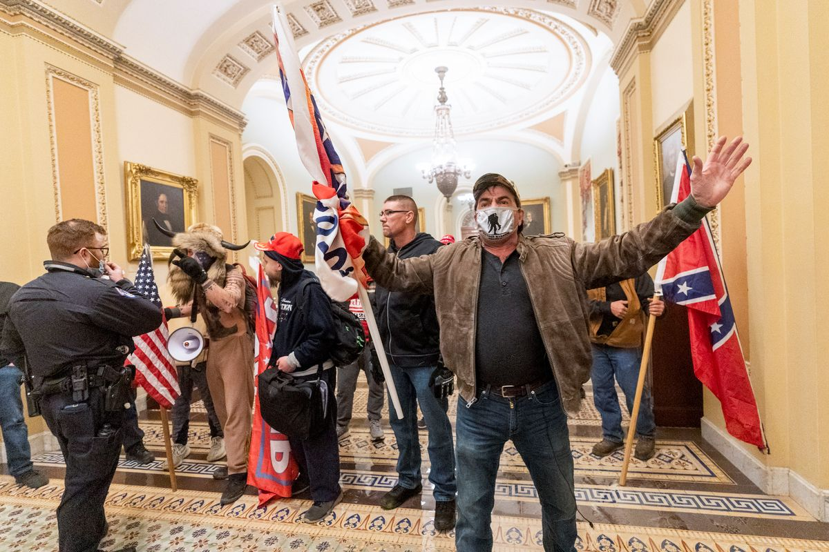 Supporters of U.S. President Donald Trump are confronted by U.S. Capitol Police officers outside the Senate Chamber inside the Capitol, Wednesday, Jan. 6, 2021 in Washington.