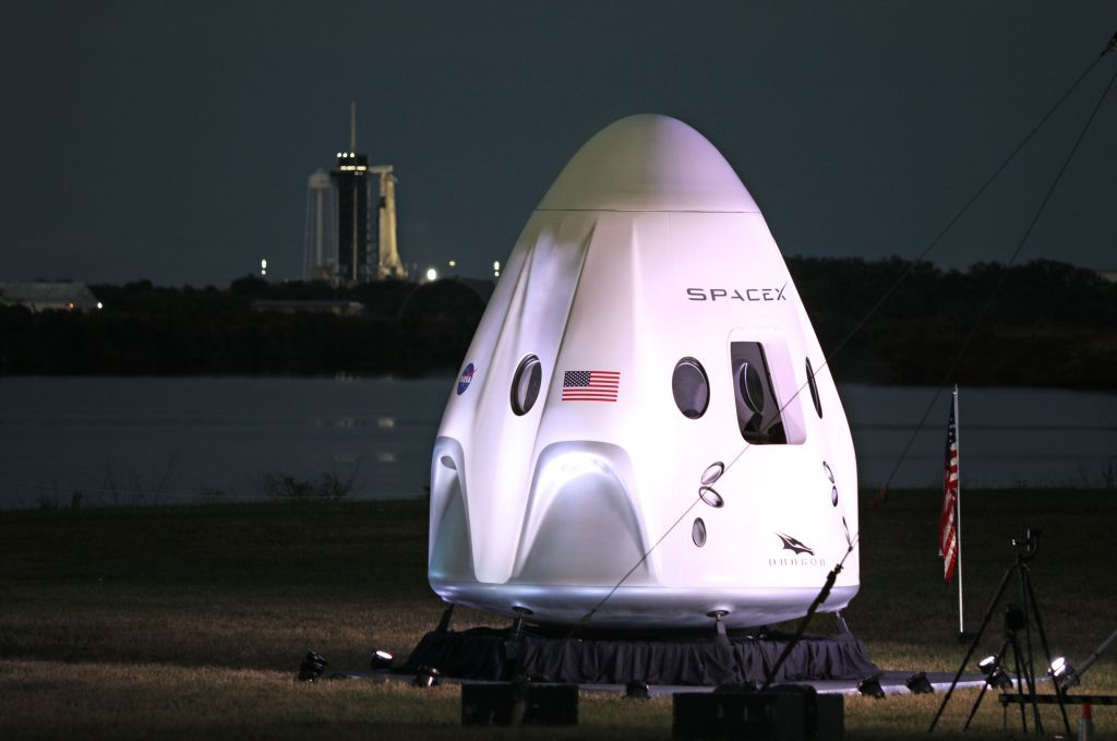 A full-size model of the Crew-1 spacecraft module sits near the launch pad as a SpaceX Falcon 9 rocket is seen at launch complex 39A in the distance at the Kennedy Space Center in Florida on November 15, 2020.