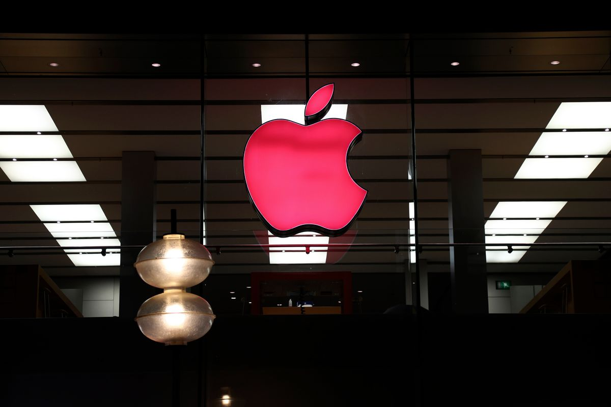 FILE - In this Sunday, Dec. 6, 2020 file photo, the logo of Apple is illuminated at a store in the city center of Munich, Germany.