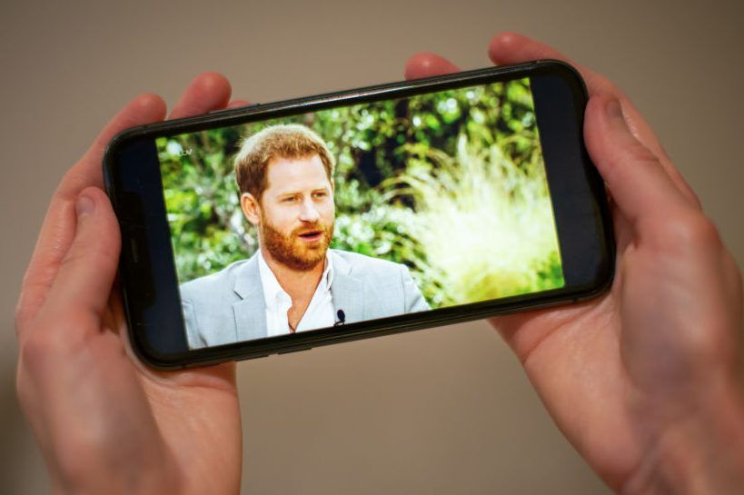 A man watches the Duke and Duchess of Sussex interview with Oprah Winfrey, which is being shown on ITV, on a phone screen in a flat in London.