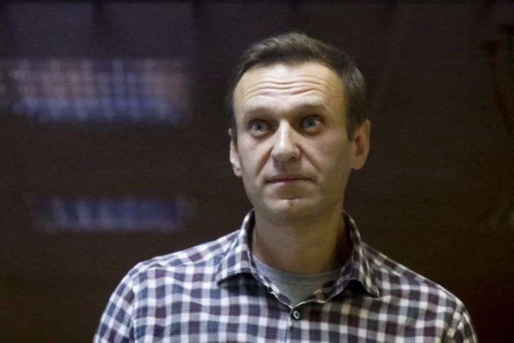 FILE - In this Saturday, Feb. 20, 2021 file photo, Russian opposition leader Alexei Navalny stands in a cage in the Babuskinsky District Court in Moscow, Russia. A doctor for imprisoned Russian opposition leader Alexei Navalny, who is in the third week of a hunger strike, said on Saturday April 17, 2021, his health is deteriorating rapidly and the 44-year-old Kremlin critic could be on the verge of death.
