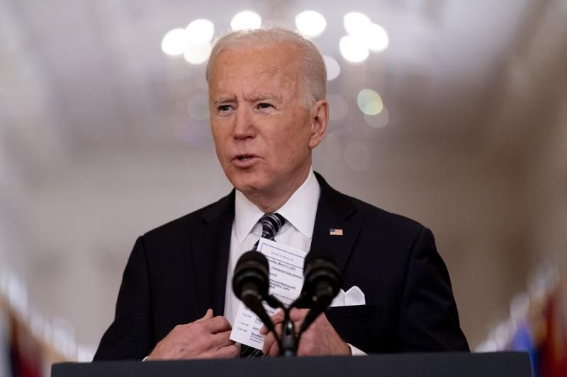 FILE - In this March 11, 2021, file photo President Joe Biden holds up a card with his daily schedule and the daily deaths from COVID-19 as he speaks about the COVID-19 pandemic during a prime-time address from the East Room of the White House in Washington.