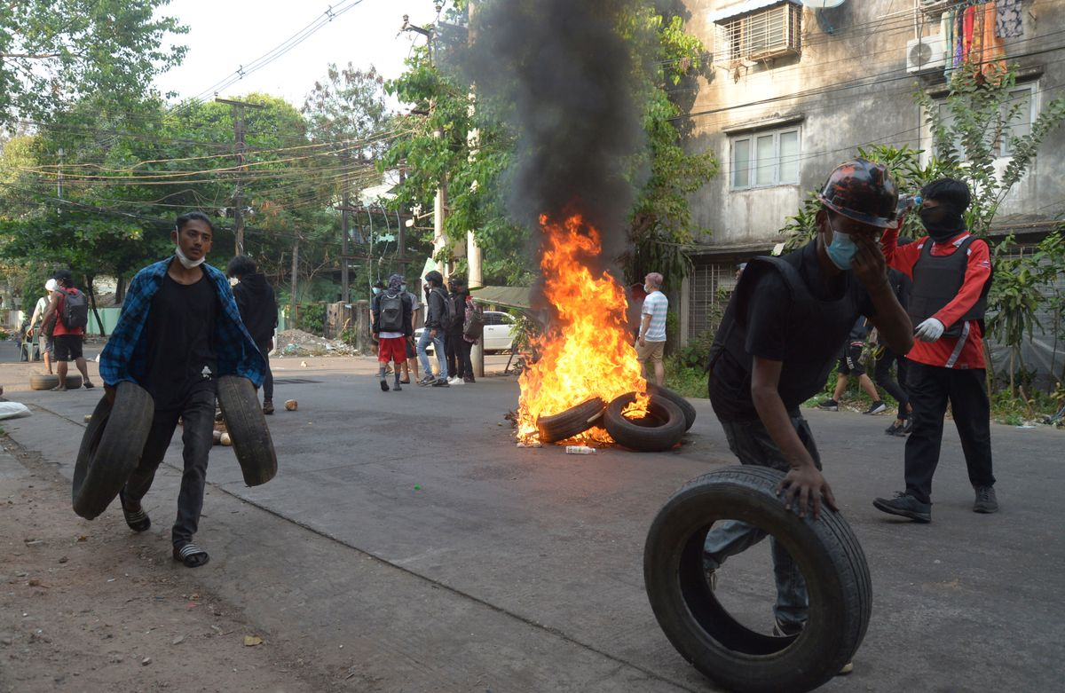 Anti-coup demonstrators gather tires to burn as the prepare to confront police during a protest in Tarmwe township, Yangon, Myanmar, Thursday, April 1, 2021.