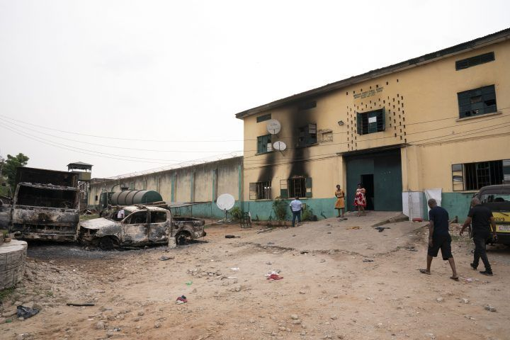 People walk past burned vehicles in front of a correctional facility in Owerri, Nigeria, on Monday, April 5, 2021. Hundreds of inmates escaped from the prison in southeastern Nigeria after a series of coordinated attacks according to government officials. (AP Photo/David Dosunmu).