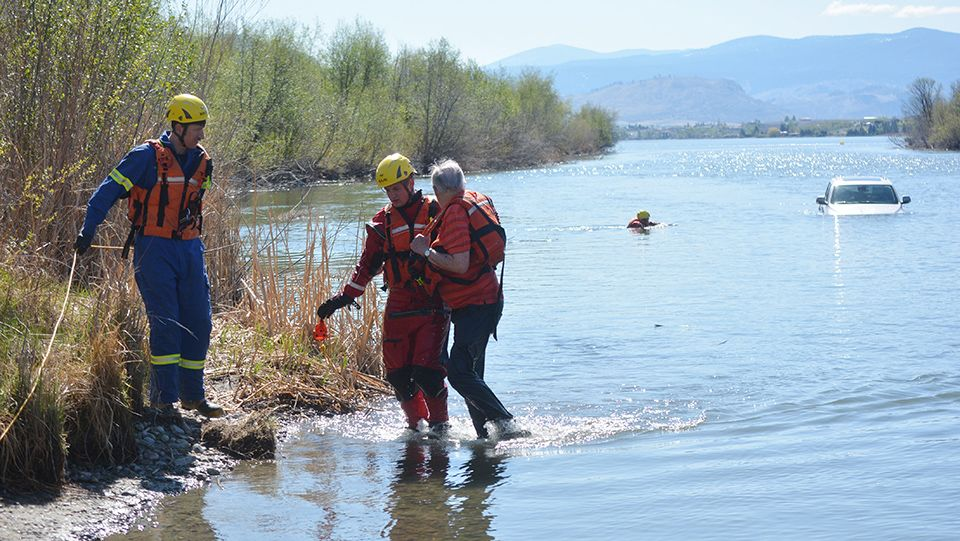 Members of the Oliver Fire Department assist an individual to shore after his vehicle was found floating in the Okanagan River channel off Road 22 Monday morning.