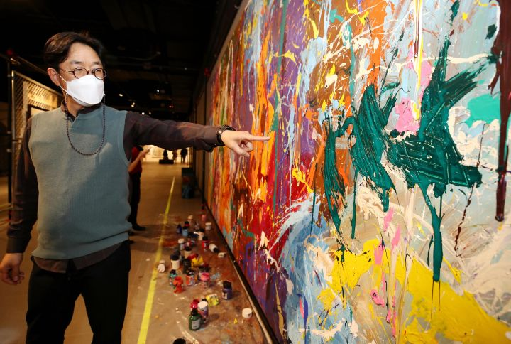 Kang Wook, head of the STREET NOISE exhibition at the Lotte World Mall, points to damage on an untitled JonOne artwork on March 28, 2021.