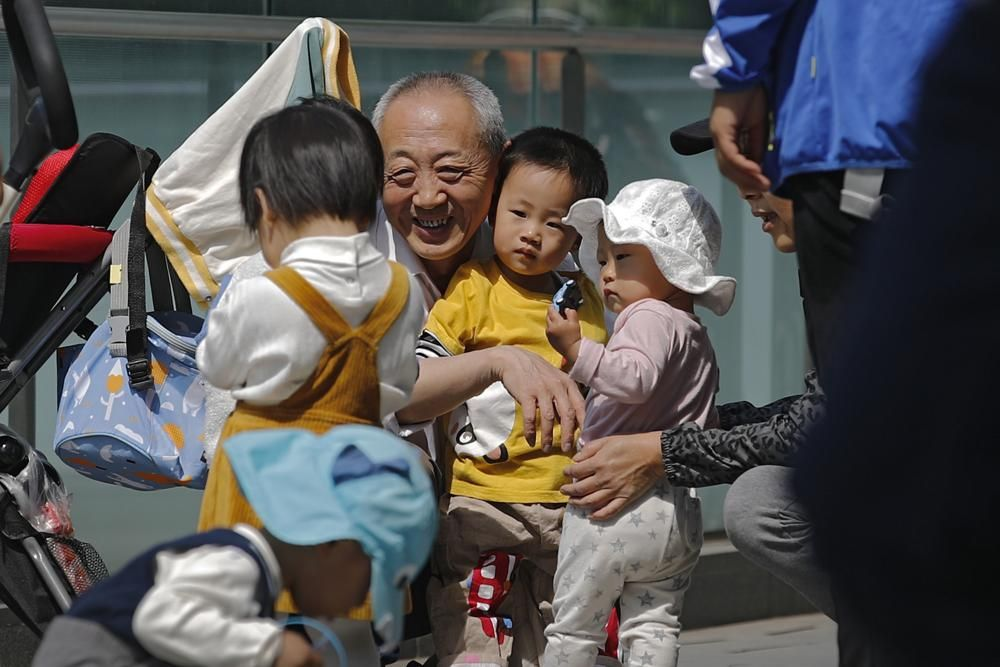 An elderly man plays with children near a commercial office building in Beijing on May 10, 2021. China's ruling Communist Party will ease birth limits to allow all couples to have three children instead of two to cope with the rapid rise in the average age of its population, a state news agency said Monday, May 31.