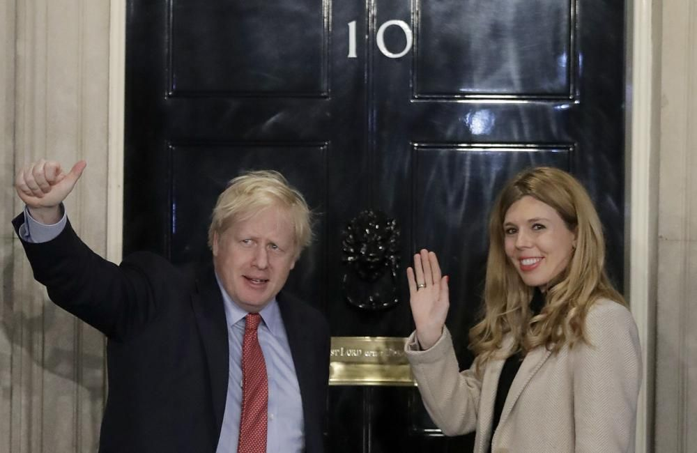 In this Friday, Dec. 13, 2019, file photo, Britain's Prime Minister Boris Johnson and his partner Carrie Symonds wave from the steps of number 10 Downing Street in London. U.K. newspapers are reporting that Prime Minister Johnson and his fiancée Symonds married Saturday, May 29, 2021, in a small private ceremony in London. The Mail on Sunday and the Sun said the couple wed at the Roman Catholic Westminster Cathedral in front of a small group of friends and family.