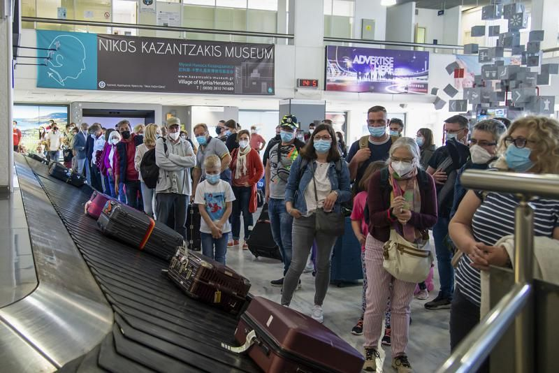 FILE - In this May 14, 2021, file photo, passengers from Hanover wait to pick their luggage at Nikos Kazantzakis International Airport in Heraklion, on the island of Crete, Greece. Coronavirus infections, hospitalizations and deaths are plummeting across much of Europe. Vaccination rates are accelerating, and with them, the promise of summer vacations.