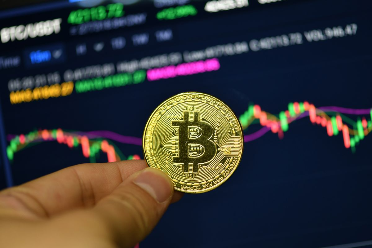 CHINA - 2021/05/20: In this photo illustration a Bitcoin is seen on display with a Bitcoin price trend chart in the background.