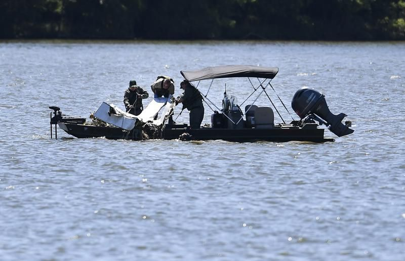 Emergency personnel remove debris from a plane crash in Percy Priest Lake Sunday, May 30, 2021, near Smyrna, Tenn. A small jet carrying seven people crashed Saturday, and authorities indicated that no one on board survived. (George Walker IV/The Tennessean via AP).