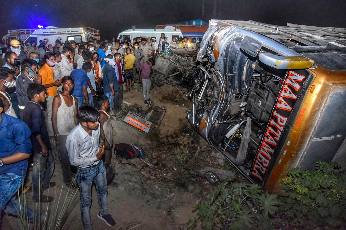 Onlookers gather near the wreckage after a bus carrying migrant workers after the lifting of coronavirus restrictions hit a delivery van on a highway near Kanpur, Uttar Pradesh state, India, Tuesday, June 8, 2021. More than a dozen people were killed. (AP Photo).