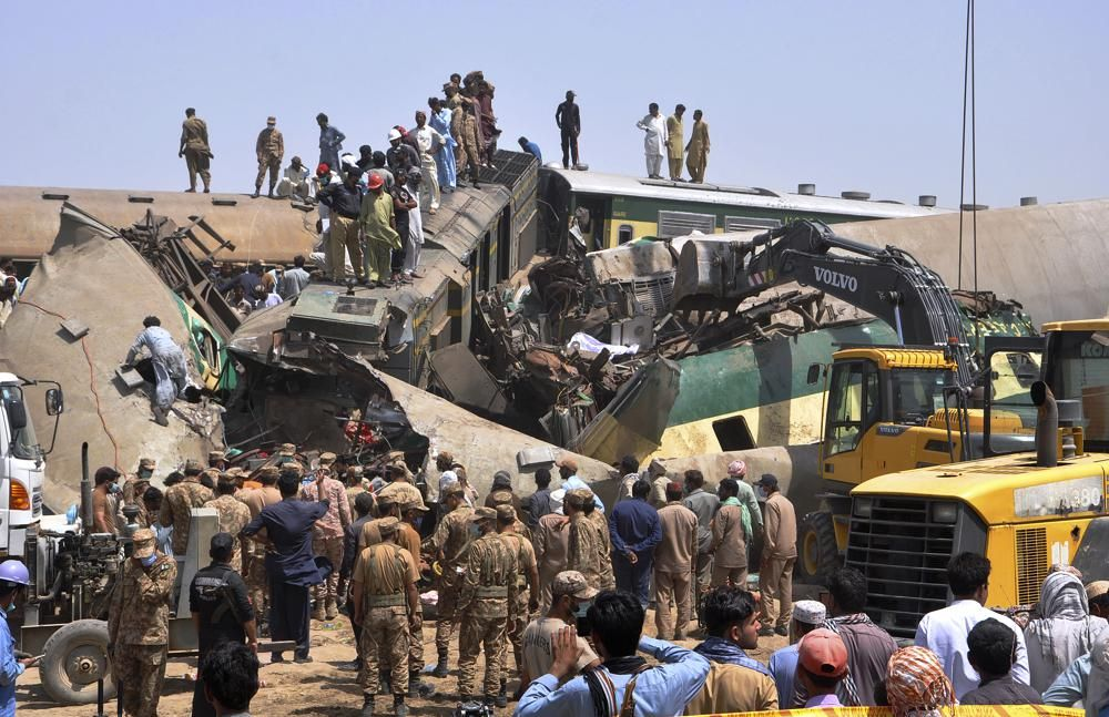 Soldiers and volunteers work at the site of a train collision in the Ghotki district in southern Pakistan, Monday, June 7, 2021.