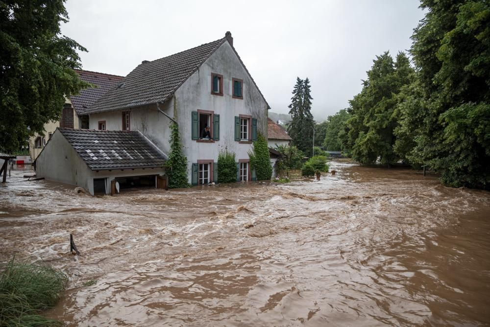 Houses are submerged on the overflowed river banks in Erdorf, Germany, as the village was flooded Thursday, July 15, 2021.
